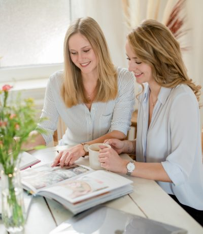 Zwei Frauen sitzen an einem Tisch und arbeiten. Sie gucken gemeinsam in ein Buch mit Hochzeits-Moodboards.